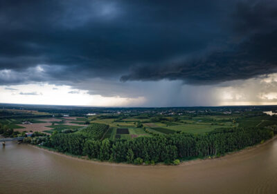 The river with a storm and a rain in the summer, Garonne river, Gironde, France